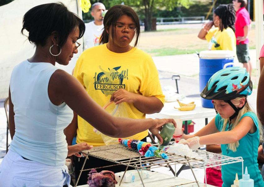 Children learn how to tie-dye at a street festival in Ferguson, Missouri, in 2012. Photo courtesy of the Ferguson Youth Initiative