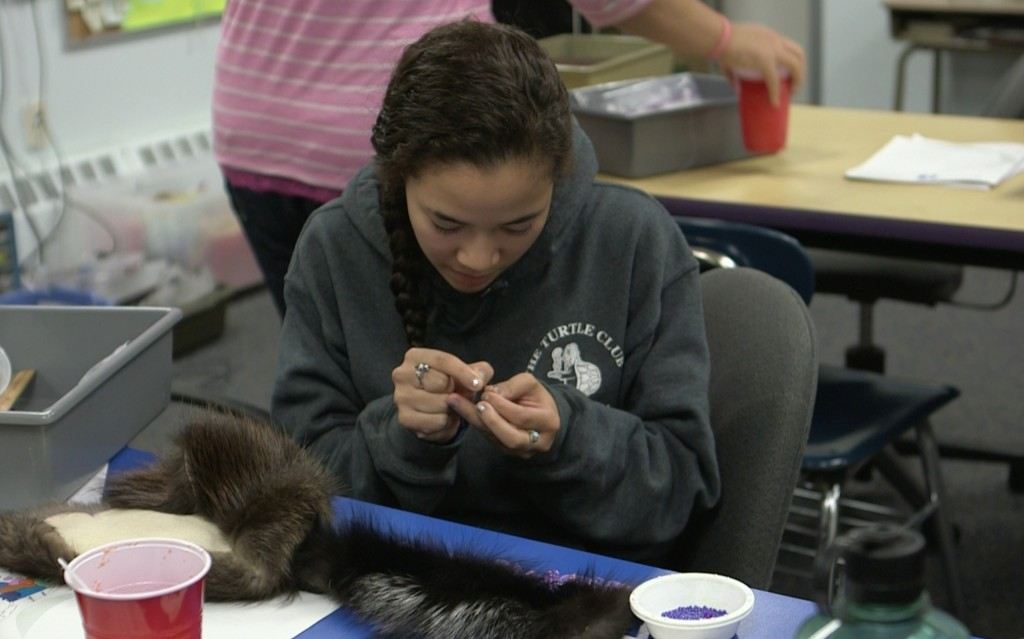 Sassa Williams, 18, works on her Yup'ik headdress at Dillingham High School in Dillingham, Alaska. Photo by Mike Fritz/PBS NewsHour