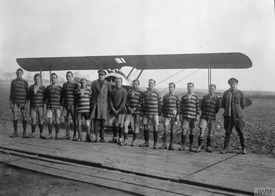 1918. The Royal Flying Corp football team of No.54 Squadron RAF line up for a team photograph in front of a Sopwith Camel aircraft. Photo courtesy Imperial War Museum via Open University