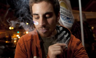 Michael Finkelstein smokes a marijuana cigarette while watching election results in Oakland, California, in 2010. Photo by David Paul Morris/Bloomberg