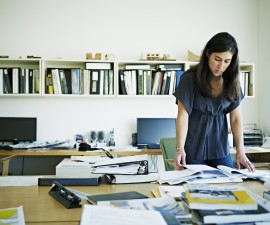 Female architect examining documents at desk. Creative image #: 107670162 License type: Rights-managed Photographer: Thomas Barwick / Getty Images