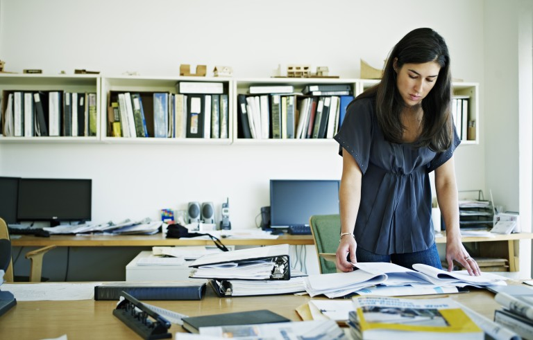 Female architect examining documents at desk. Creative image #: 107670162 License type: Rights-managed Photographer: Thomas Barwick / Getty Images