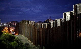 The border wall illuminated at night in Nogales, Arizona on July 6, 2012. Photo by Sandy Huffaker/Getty Images