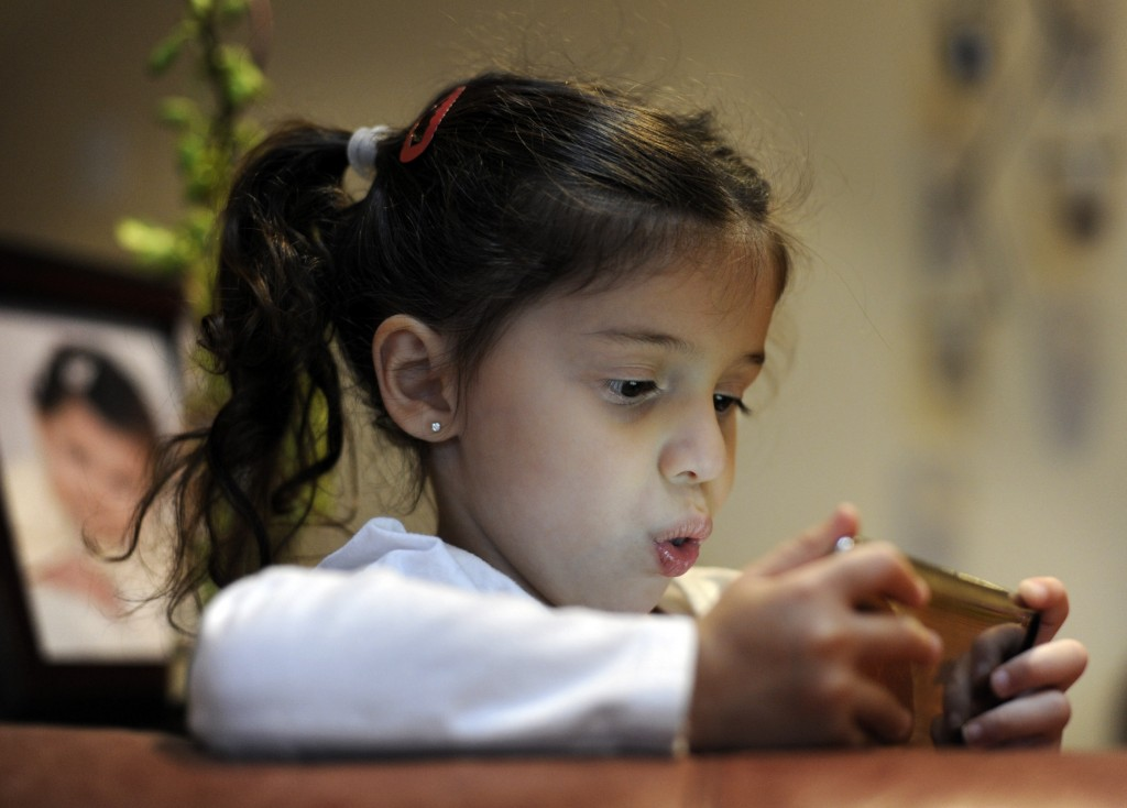 Two-year-old Maggie Awad, plays an app game  on her mother's, Paula Mansour, IPod Touch, at their home in Falls Church, Virginia. App makers collect information about kids, often without parental consent. Photo by Melina Mara/The Washington Post