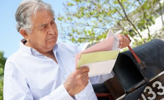 Worried Senior Man Checking Mailbox