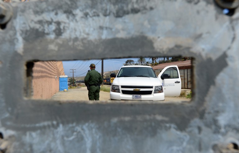 A U.S. Border Patrol agent, seen through an opening in a fence, keeps watch on the 'border fence' near the San Ysidro port of entry along the US-Mexico border near San Diego, California. Photo by Frederic J. Brown/AFP/Getty Images