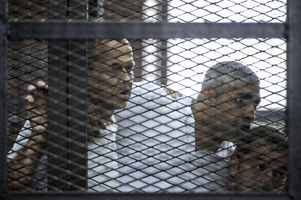Al Jazeera journalists Peter Greste, Mohamed Fadel Fahmy and Baher Mohamed listen to the verdict inside the defendants cage during their trial for allegedly supporting the Muslim Brotherhood on June 23, 2014.