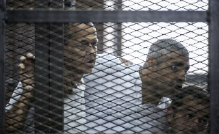 Al-Jazeera journalists Peter Greste, Mohamed Fadel Fahmy and Baher Mohamed listen to the verdict inside the defendants cage during their trial for allegedly supporting the Muslim Brotherhood on June 23, 2014.