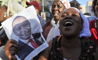 Supporters of Kenya's President Uhuru Kenyatta celebrate in the streets of Nairobi following the International Criminal Court's ruling to drop crimes against humanity charges against him at the Hague on Dec. 5. Photo by Simon Maina/AFP/Getty Images