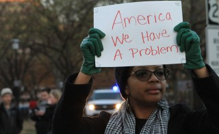 A woman holds a banner during a march throughout downtown in Washington, United States on December 7, 2014 to protest the killings of unarmed black men by police officers. Photo by Michael Hernandez/Anadolu Agency/Getty Images