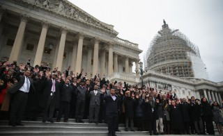Black congressional staffers hold their hands up as they pose for a group photo during a walkout December 11, 2014 on the steps of the U.S. Capitol in Washington, DC. The staffers staged a walkout to protest over the recent Mike Brown and Eric Garner grand jury decisions. Photo by Alex Wong/Getty Images