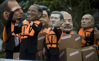 Activist depicting Australia's Prime Minister Tony Abbot (L), US President Barack Obama (2-L), China's President Xi Jinping (3-L), Canada's Prime Minister Stephen Harper (C), India's Prime Minister Narendra Modi (3-R), Rusia's President Vladimir Putin (2-R) and Japan's Prime Minister Shinzo Abe (R) demonstrate on the sidelines of the UN COP20 and CMP10 climate change conferences being held in Lima on December 12, 2014. The UN 20th session of the Conference of the Parties on Climate Change (COP20), and the 10th session of the Conference of the Parties serving as the Meeting of the Parties to the Kyoto Protocol (CMP10) entered its second week of negotiations until 12th. AFP PHOTO/Eitan Abramovich        (Photo credit should read EITAN ABRAMOVICH/AFP/Getty Images)