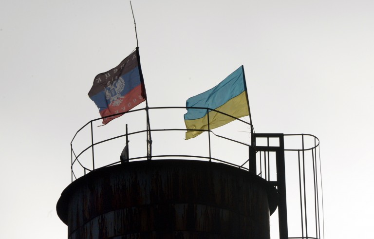 Flags of Ukraine (R) and of the self-proclaimed People's Republic of Donetsk fly on a water tower in the city of Krasny Partizan near Donetsk on December 13, 2014. Russia responded angrily on December 13 to news that US senators had passed a bill calling for fresh sanctions against Moscow and the supply of lethal military aid to Ukraine. Photo by Vasily Maximov/AFP/Getty Images