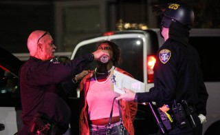OAKLAND, CA - DECEMBER 13:  Mikela Mosley is given water during her arrest following a 'Millions March' demonstration protesting the killing of unarmed black men by police on December 13, 2014 in Oakland, California. The march was one of many held nationwide. (Photo by Elijah Nouvelage/Getty Images)