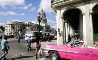 An American vintage car drives in front of the Capitolio in Havana, Cuba, shortly after a live broadcast a speech by Cuban President Raul Castro about the re-establishment of official diplomatic relations with the U.S. on December 17, 2014. Photo by Sven Creutzmann/Getty Images