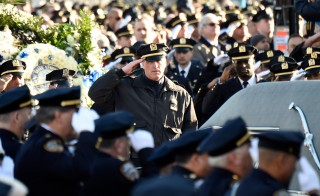 New York City Police Officers salute at the funeral of slain New York City Police Officer Rafael Ramos, one of two officers murdered while sitting in their patrol car in an ambush in Brooklyn last Saturday afternoon on December 27, 2014 in New York City. Thousands of fellow officers, family, friends and Vice President Joseph Biden are expected at the church in the Glendale neighborhood of Queens for the funeral. (Photo by Kevin Mazur/Getty Images)