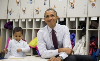 U.S. President Barack Obama sits with students during a tour of a Pre-K classroom at Powell Elementary School prior to speaking on the Fiscal Year 2015 budget in Washington, D.C. in March 2014. Photo by Saul Loeb/AFP/Getty Images