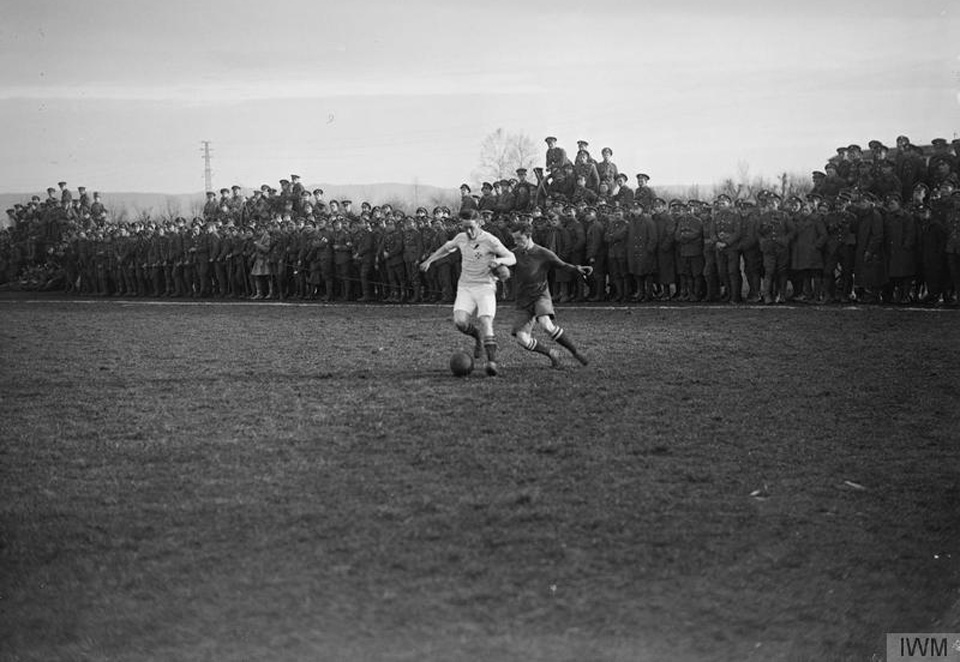 Final of the 48th Divisional Fanshawe Cup. The 1/7th Battalion Worcestershire Regiment versus 1/7th Battalion Royal Warwickshire Regiment. Two players tackle for the ball as soldiers scramble to get a view on the Italian Front, Trissino, Italy in 1918. Photo courtesy of Imperial War Museum