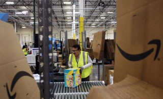 An Amazon worker pushes a box of diapers along a conveyor belt at the Amazon.com Phoenix Fulfillment Center in Goodyear, Arizona. The Supreme Court ruled today that the company does not have to pay its workers for time spent waiting to pass through security checks at the end of their shifts. Photo by Joshua Lott/Bloomberg