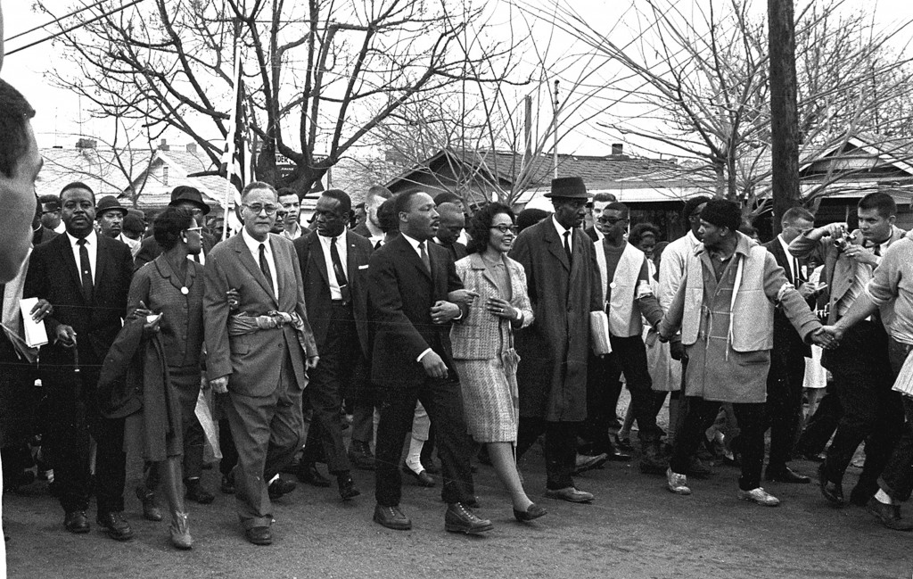 American Civil Rights leader Dr. Martin Luther King Jr. (1929 - 1968) and his wife Coretta Scott King (1927 - 2006) (center, arm in arm) lead others during on the Selma to Montgomery marches held in support of voter rights, Alabama, late March, 1965. Among those with them are Reverend Ralph Abernathy (1926 - 1990) (at left, facing camera), and Pulitzer-Prize winning political scientist and diplomat Ralph Bunche (1904 - 1971) (front row, third left with glasses) whose his wife, Ruth (nee Harris, 1906 - 1988), holds his arm. (Photo by Robert Abbott Sengstacke/Getty Images)