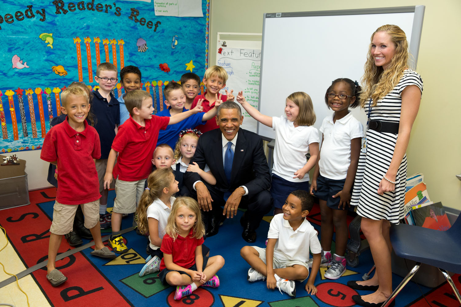 A group of students gives the president rabbit ears in a group photo taken at an elementary school at MacDill Air Force Base in Tampa, Florida. Official White House photo by Pete Souza.
