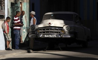 Cubans talk near a broken car in Havana December 19, 2014. Photo by REUTERS/Enrique De La Osa
