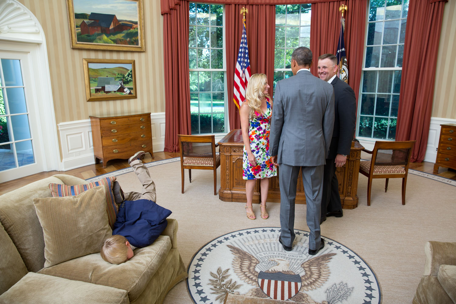 A young boy face-plants onto the sofa in the Oval Office as the president greets his parents - a departing United States Secret Service agent and his wife. Official White House photo by Lawrence Jackson.