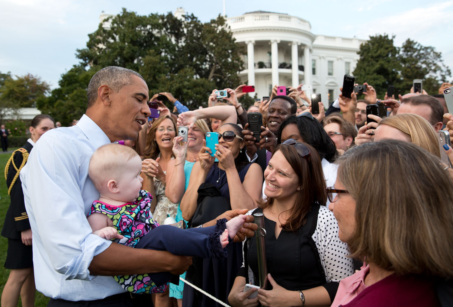 The President checks out a baby's foot while greeting guests at a picnic on the South Lawn of the White House. Official White House photograph by Pete Souza.