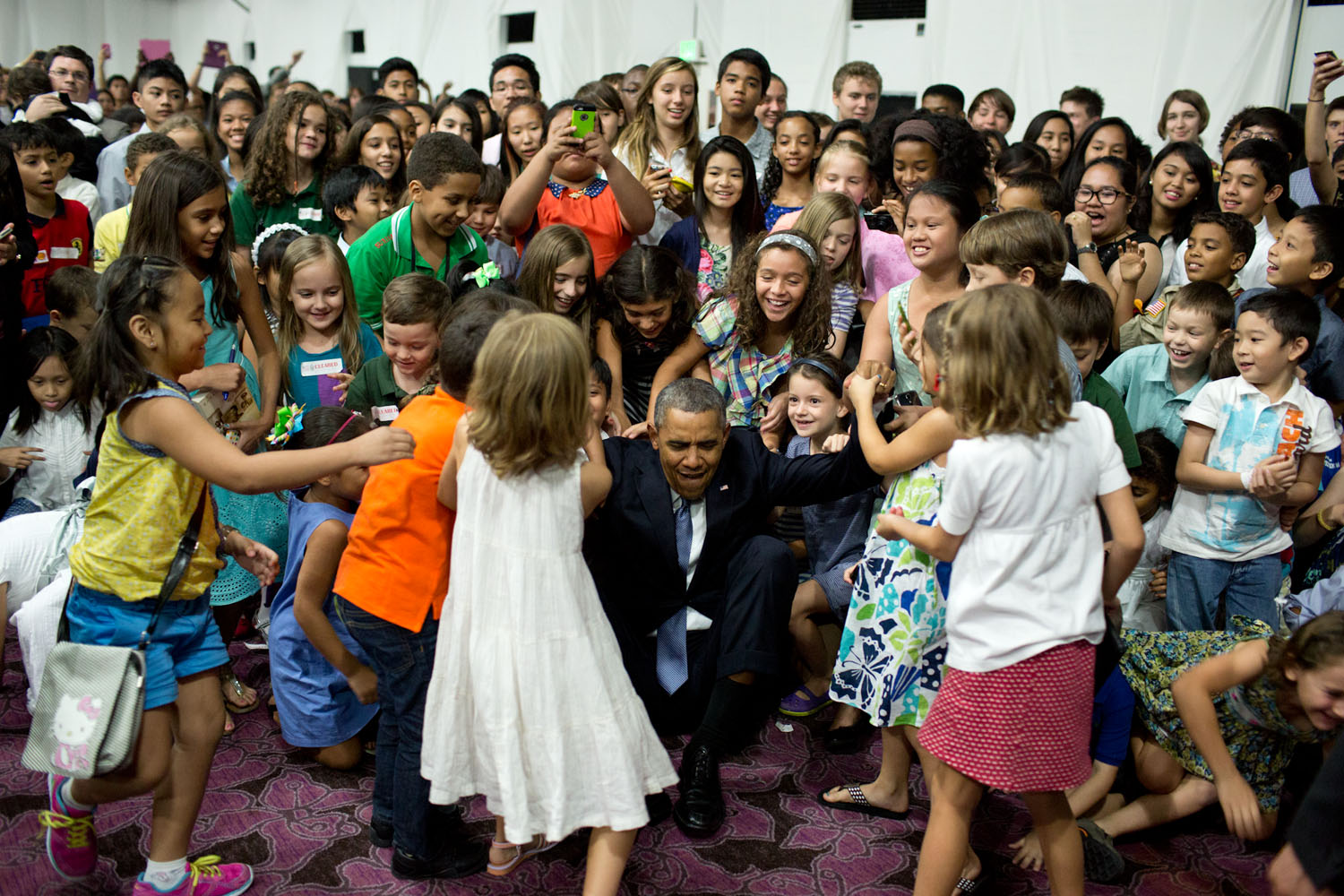 Students help the president up after posing for a photograph at the U.S. Embassy in Manila, the Philippines. Official White House photo by Pete Souza.