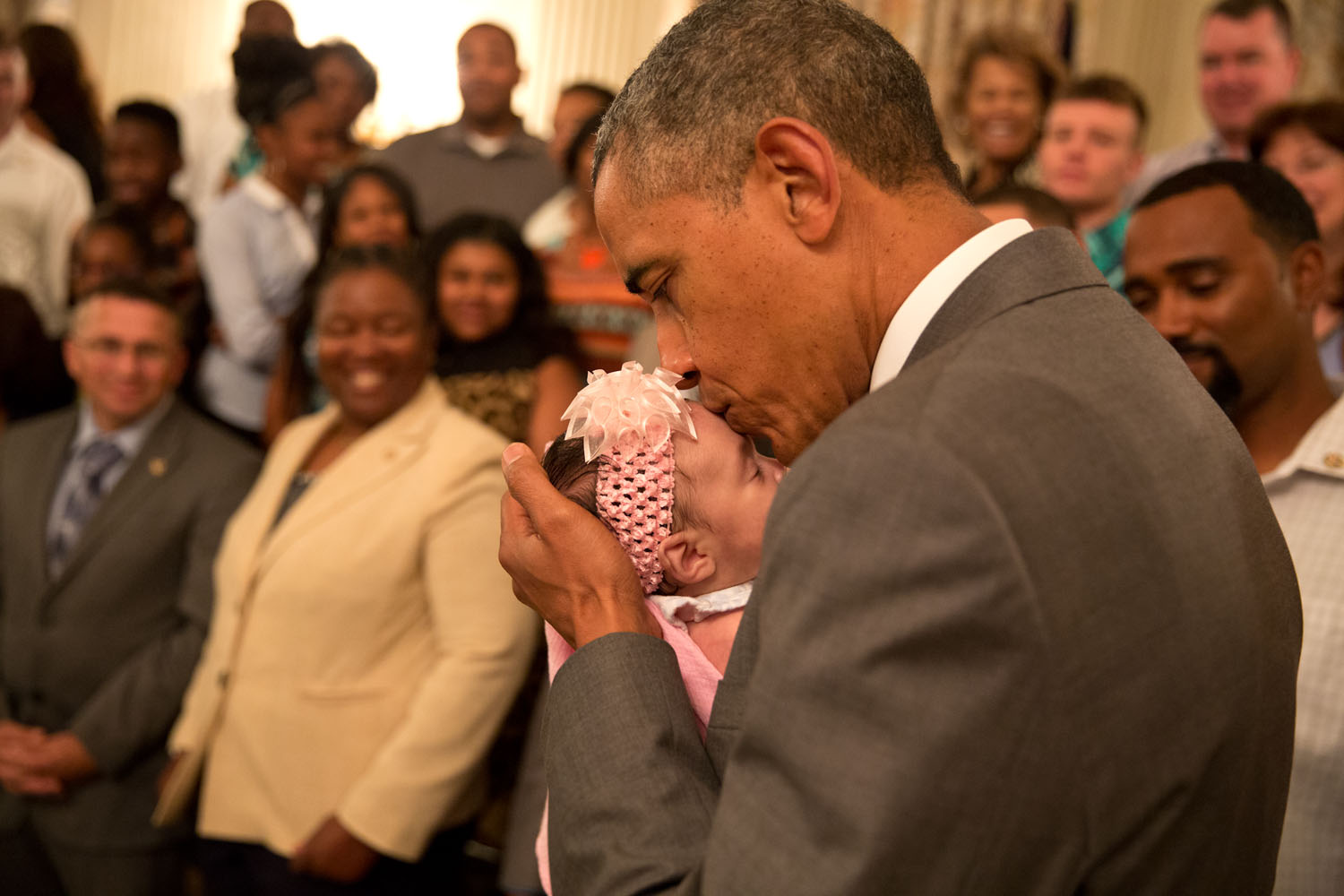 The President kisses a baby girl as he and the Vice president greet wounded warriors and their families during their tour in the East Room of the White House. Official White House photo by Pete Souza.