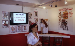 Waitress Elisha Greenleaf walks past a monitor advertising a calorie count at Heart Attack Grill in Chandler, Arizona June 17, 2009. The restaurant is known for its hospital theme and triple and quadruple bypass burgers. Photo by Joshua Lott/Reuters