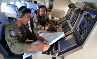 Two members of the Indonesian Navy help with the search for AirAsia flight QZ 8501 on board a CN235 aircraft over Karimun Java, in the Java Sea on December 28, 2014. Photo by Antara Foto/Reuters
