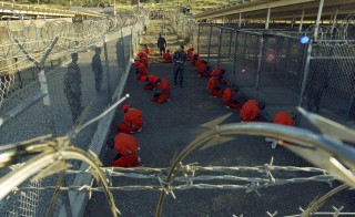 Detainees in orange jumpsuits sit in a holding area under the watchful eyes of military police during in-processing to the temporary detention facility at Camp X-Ray of Naval Base Guantanamo Bay in this January 11, 2002 Photo by Reuters