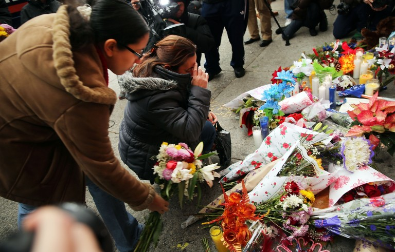 Women place flowers at a memorial to the two New York Police Department  officers that were shot and killed nearby December 21, 2014 in the Bedford Stuyvesant neighborhood of Brooklyn. Credit: Spencer Platt/Getty Images