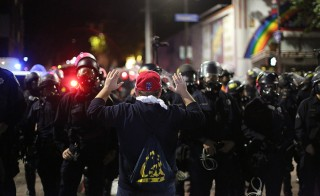 A protester on Telegraph Avenue in Berkeley faces police with his hands up during Saturday night's protest. Photo by Patrick Chong/Daily Californian