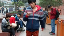 People check their mobile phones in a plaza in Shanghai, China. Photo by Larisa Epatko/PBS NewsHour