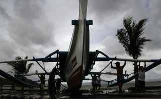 Fishermen carry thier outrigger to higher ground in Legazpi City, south of Manila on December 5, 2014, ahead of the landfall of Typhoon Hagupit. Thousands of people in the Philippines sought shelter in churches, schools and other makeshift evacuation centres on December 5 as monster Typhoon Hagupit bore down on the disaster-weary nation. (Credit: Charism SAYAT/AFP/Getty Images)