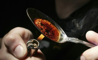 Re-enactment of heroin user burning heroin on spoon