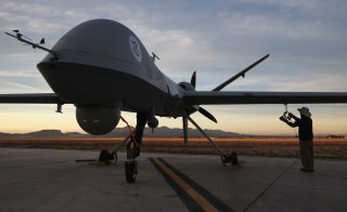 Maintenance personnel check a Predator drone operated by U.S. Office of Air and Marine, part of U.S. Customs and Border Protection, before its surveillance flight near the Mexican border on March 7, 2013 from Fort Huachuca in Sierra Vista, Arizona. Photo by John Moore/Getty Images