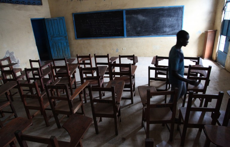 A boy walks through an empty classroom in Monrovia, Liberia, on July 31, 2014. The school, like others throughout the country, was closed to protect students from contracting Ebola. Photo by stringer/AFP/Getty Images
