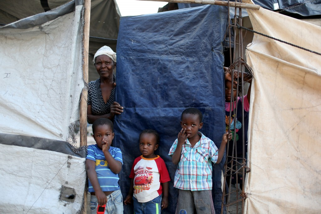 photo essay s earthquake victims wonder where the  a family looks out from behind the tarp that serves as the front door to their