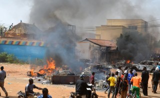 "People gather next to rubbles and a hotel set on fire during a demonstration against French weekly Charlie Hebdo's publication of a cartoon of the Prophet Mohammed in Niamey, on January 17, 2015.  At least 1,000 youths assembled at the grand mosque in the capital Niamey, some of them throwing rocks at police while others burned tyres and chanted ""Allahu Akbar"" (""God is Greatest""). The protest came a day after a policeman and three civilians were killed and 45 injured in protests against Charlie Hebdo in Niger's second city of Zinder, which saw three churches ransacked and the French cultural centre burned down. AFP PHOTO / BOUREIMA HAMA        (Photo credit should read BOUREIMA HAMA/AFP/Getty Images)"