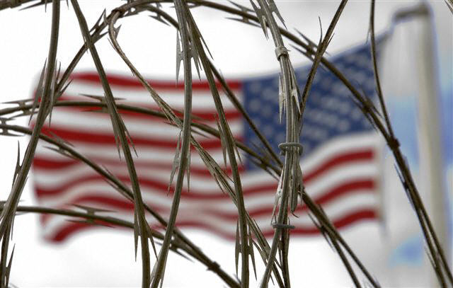 The US flag flies above the Camp Delta maximum security area in December 2006 on the US Naval Base at Guantanamo Bay, Cuba.  Image by Paul J. Richards/AFP/Getty Images
