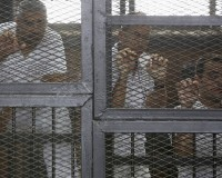 Al Jazeera journalists Mohammed Fahmy, Peter Greste and Baher Mohamed stand behind bars at a court in Cairo