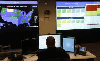 A U.S. Department of Homeland Security employee works in front of a U.S. threat level map and monitoring display inside the National Cybersecurity and Communications Integration Center during a guided media tour in Arlington, Virginia. Photo by Kevin Lamarque/Reuters