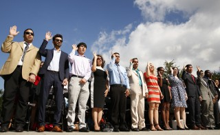 New U.S. citizens raise their hands as they take an oath of allegiance during a special naturalization ceremony held at the Martin Luther King Jr. Memorial in Washington on August 28, 2014. Photo by REUTERS/Kevin Lamarque