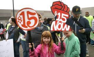 A young girl holds up signs during a rally to show support for Walmart workers on Black Friday outside the Walmart store in Lakewood, Colorado, in November. The signs refer to the strikers' demand to have a $15 minimum wage for Walmart employees. Photo by Rick Wilking/Reuters