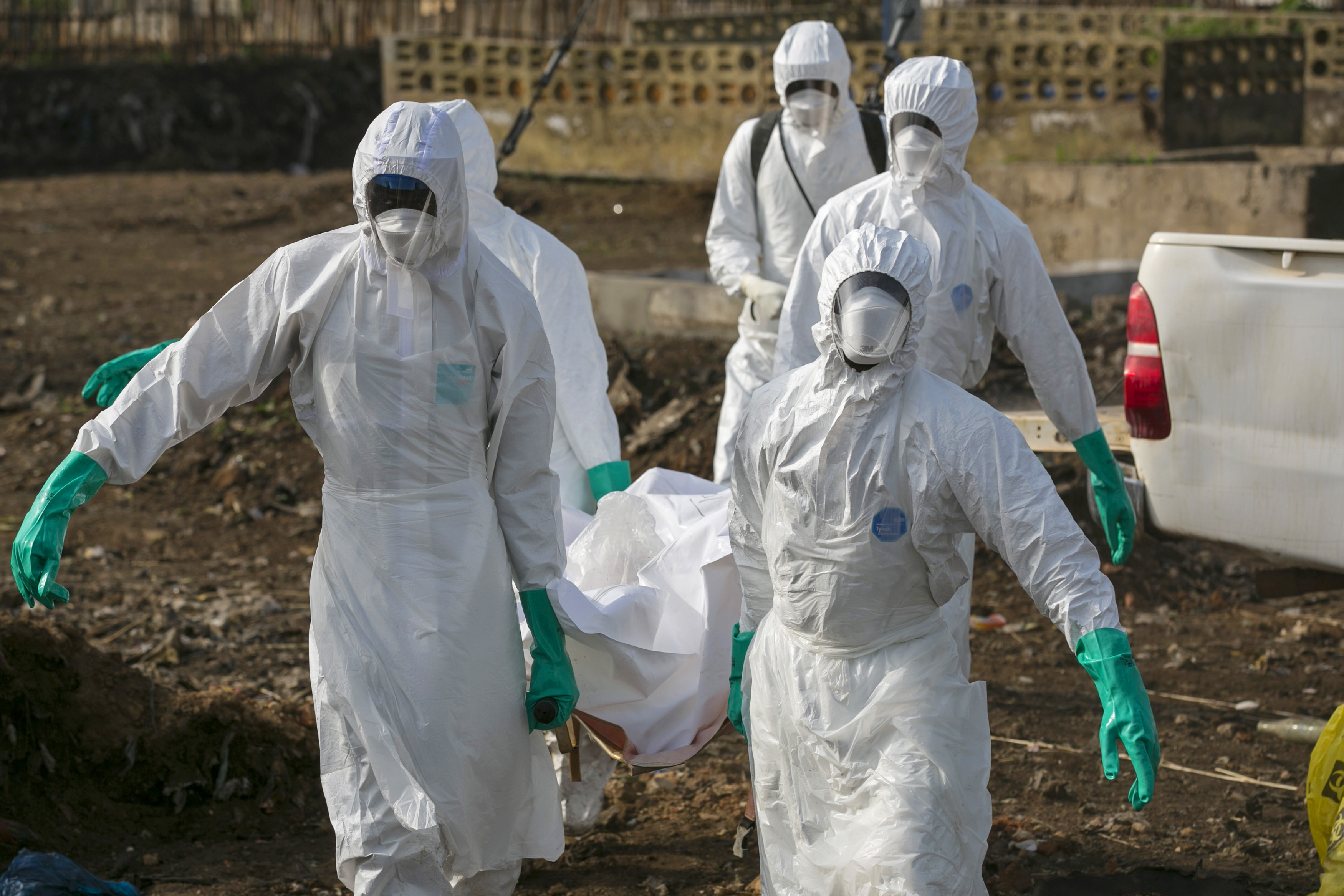 Health workers carry the body of a suspected Ebola victim for burial at a cemetery in Freetown, Sierra Leone on Dec. 21, 2014. Photo by Baz Ratner