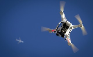 An airplane flies over a drone Jan. 1, 2015. Photo by Carlo Allegri/Reuters