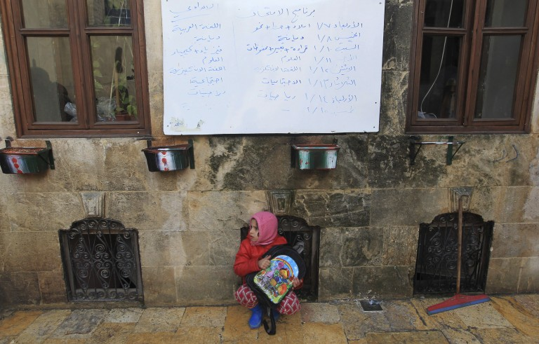 A girl sits under a whiteboard inside a school in Old Aleppo on Jan. 3, 2015. Photo by Jalal Al-Mamo/Reuters